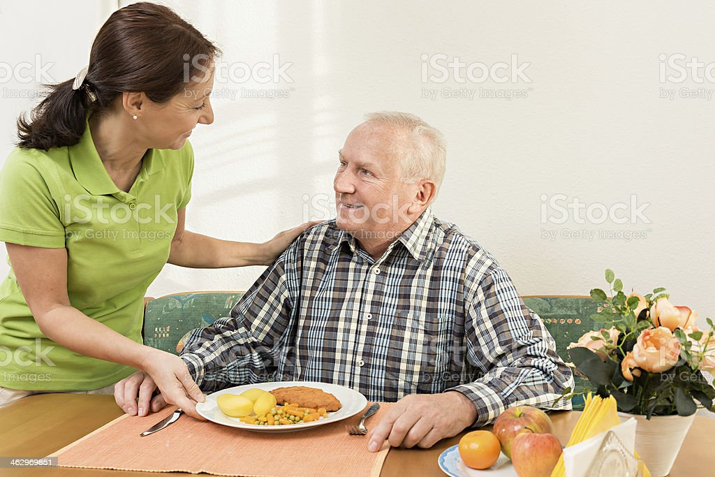 Carer giving senior man lunch in the kitchen royalty-free stock photo