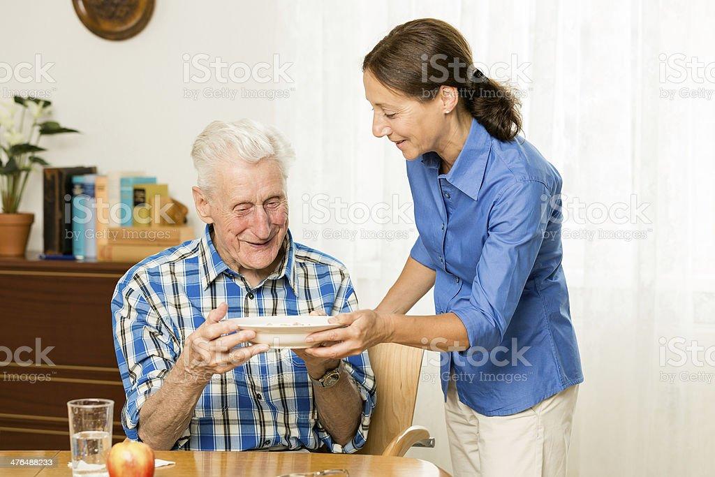 Carer giving senior man lunch royalty-free stock photo