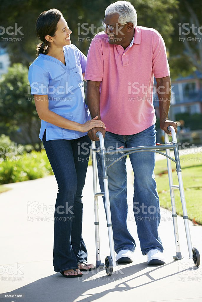Carer Helping Senior Man With Walking Frame stock photo