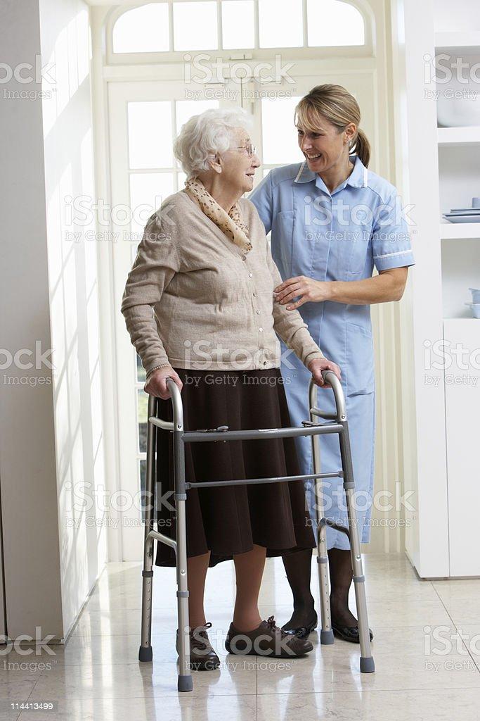 Carer Helping Senior Woman Using Walking Frame stock photo