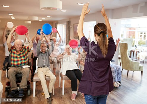 1047537292 istock photo Carer Leading Group Of Seniors In Fitness Class In Retirement Home 1047537034