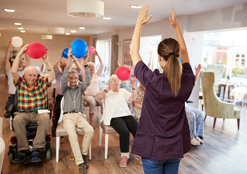 istock Carer Leading Group Of Seniors In Fitness Class In Retirement Home 1047537034