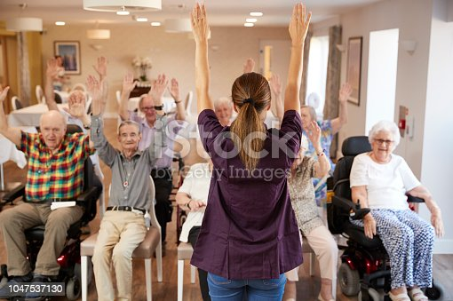 1047537292 istock photo Carer Leading Group Of Seniors In Fitness Class In Retirement Home 1047537130