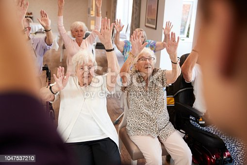 1047537292 istock photo Carer Leading Group Of Seniors In Fitness Class In Retirement Home 1047537210