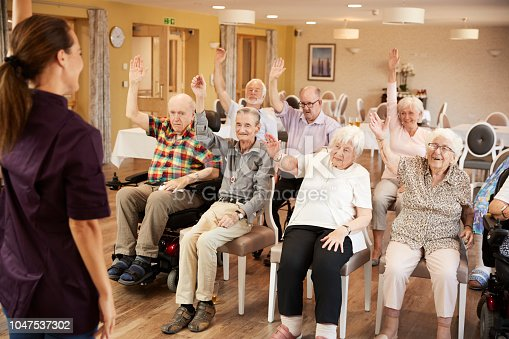 1047537292 istock photo Carer Leading Group Of Seniors In Fitness Class In Retirement Home 1047537302