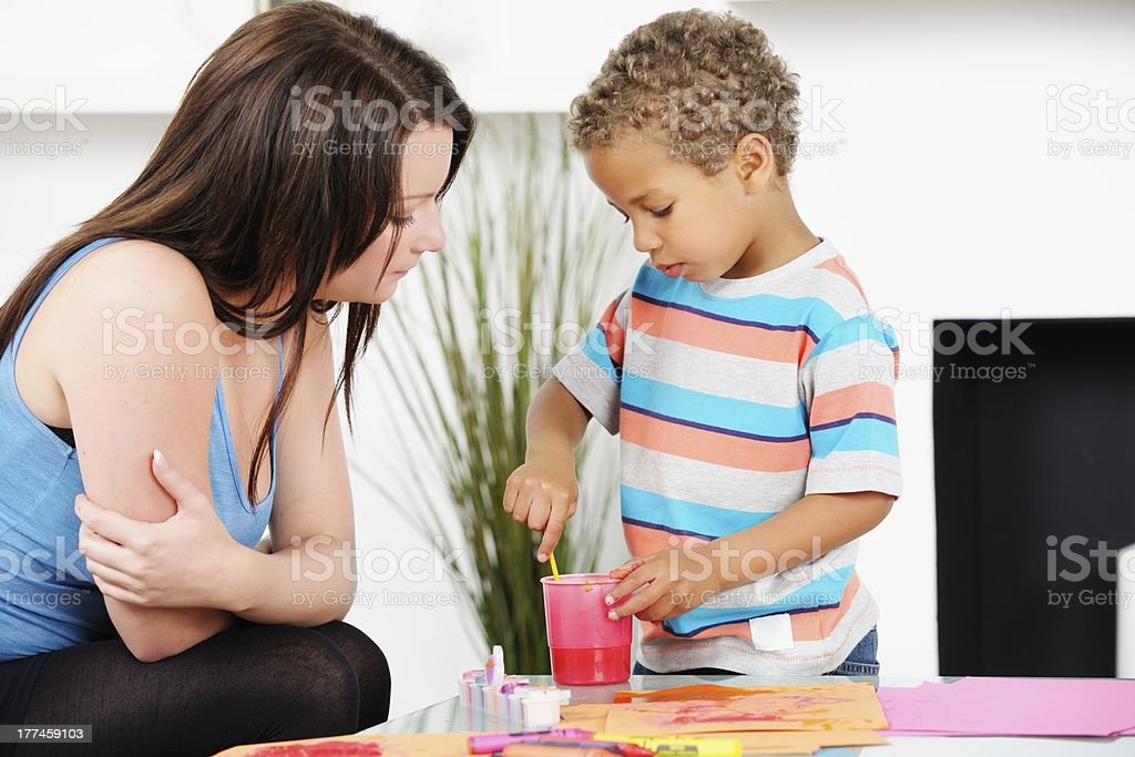 Carer/ Mother Supervising Biracial Little Boy While He Cleans Brush royalty-free stock photo