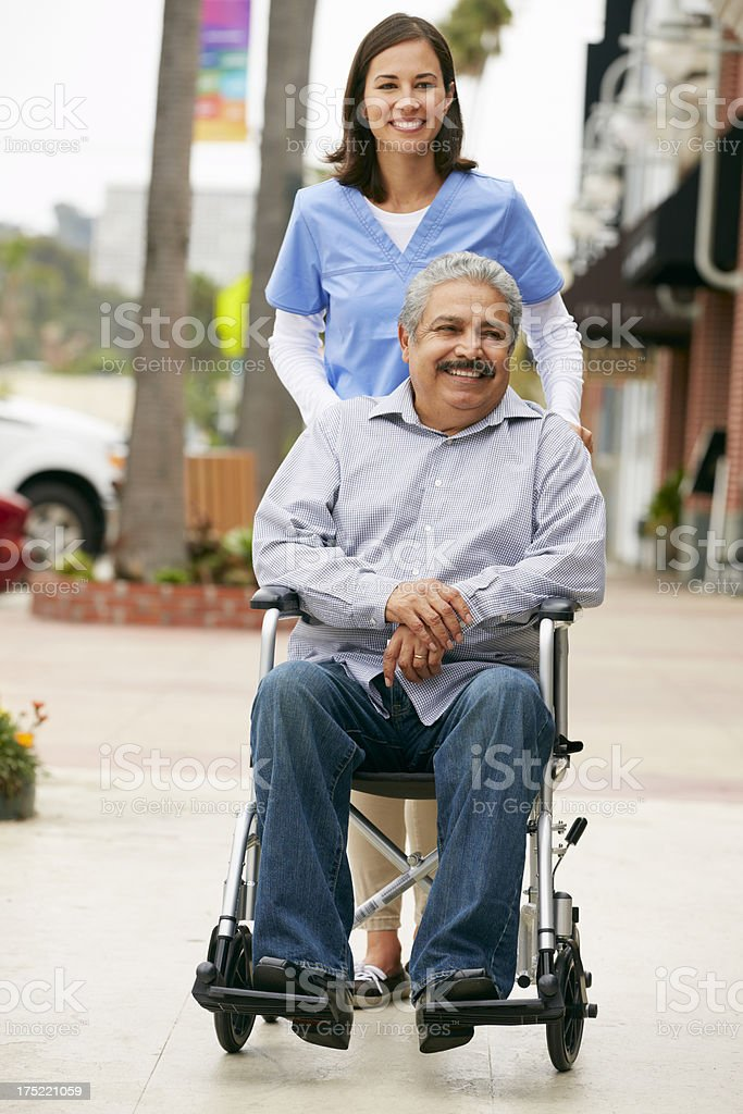 Carer Pushing Disabled Senior Man In Wheelchair royalty-free stock photo