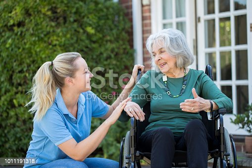 istock Carer Pushing Senior Woman In Wheelchair Outside Home 1011191318