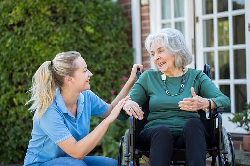 Carer Pushing Senior Woman In Wheelchair Outside Home — стоковые фотографии и другие картинки 20-29 лет