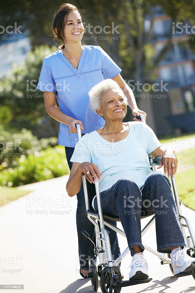 Carer Pushing Senior Woman In Wheelchair stock photo