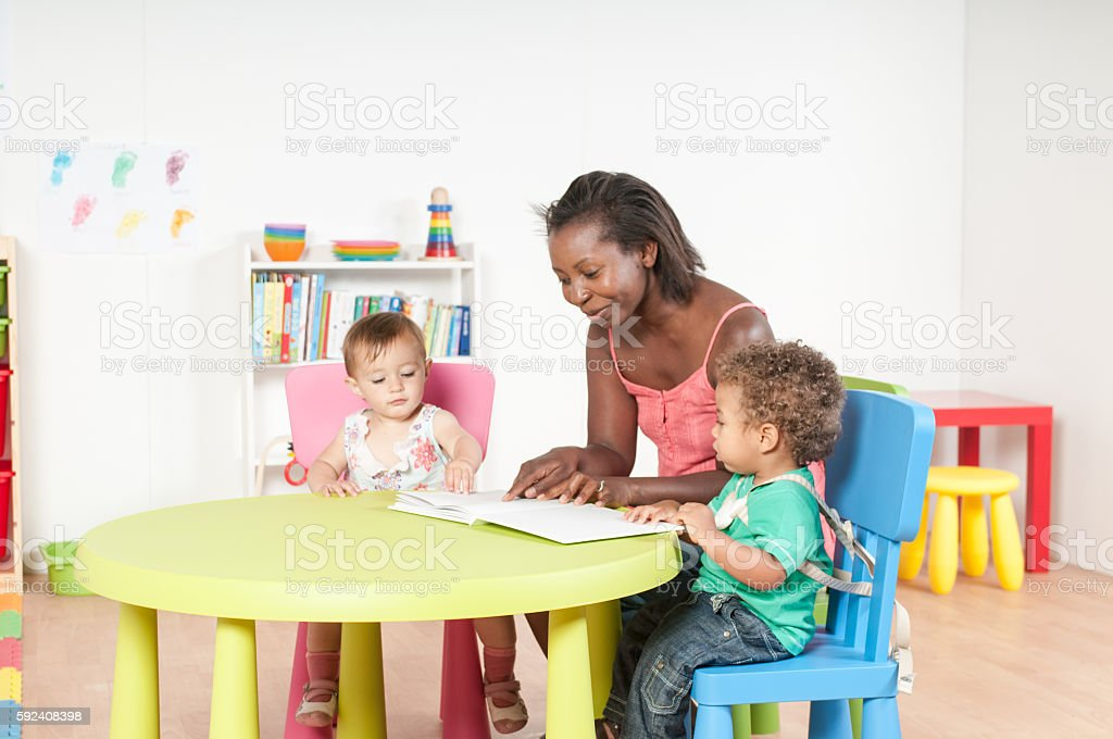Carer Reading to Toddlers in a Nursery stock photo