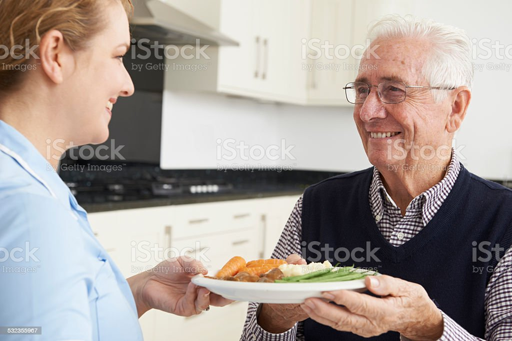 Carer Serving Lunch To Senior Man stock photo