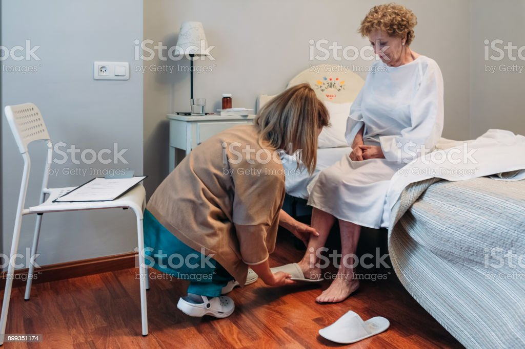 Carer wearing slippers to elderly patient stock photo