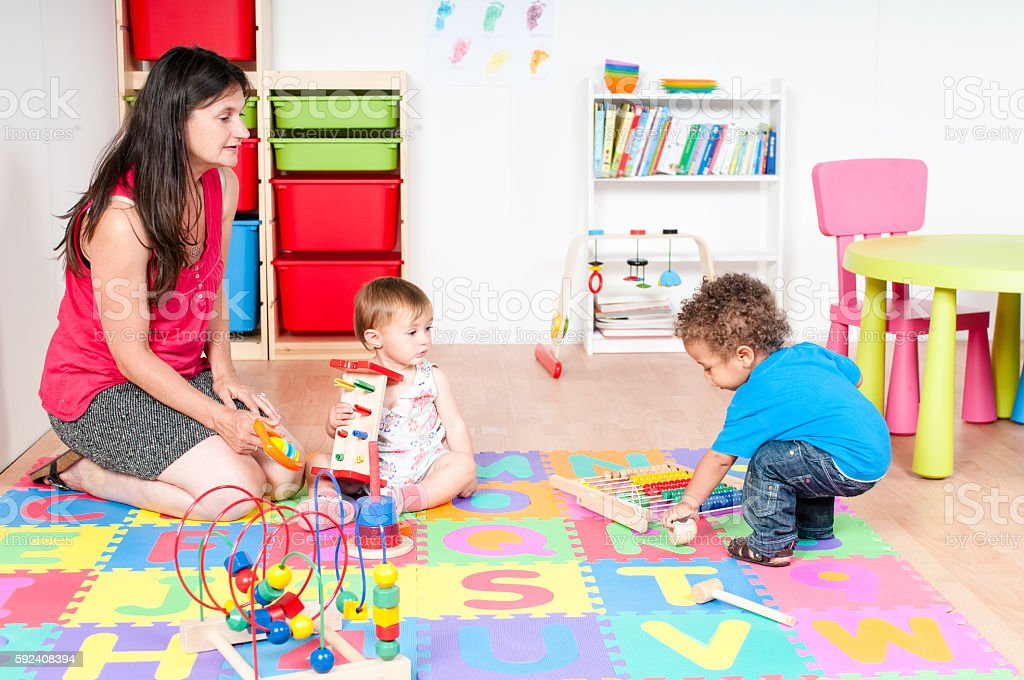 Carers And Babies/ Toddlers Playing in Nursey stock photo