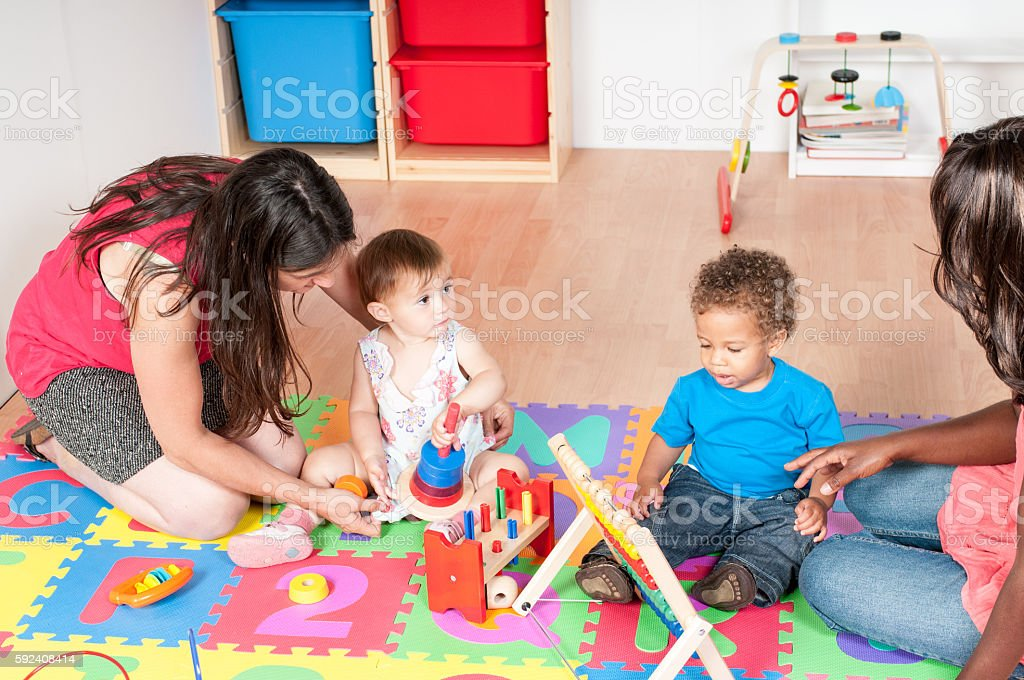 Carers And Babies/ Toddlers Playing stock photo
