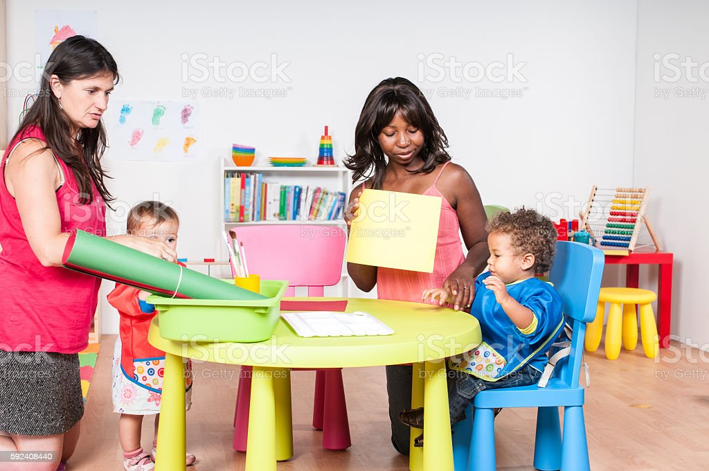 Carers And Babies/ Toddlers Preparing for Finger Painting stock photo