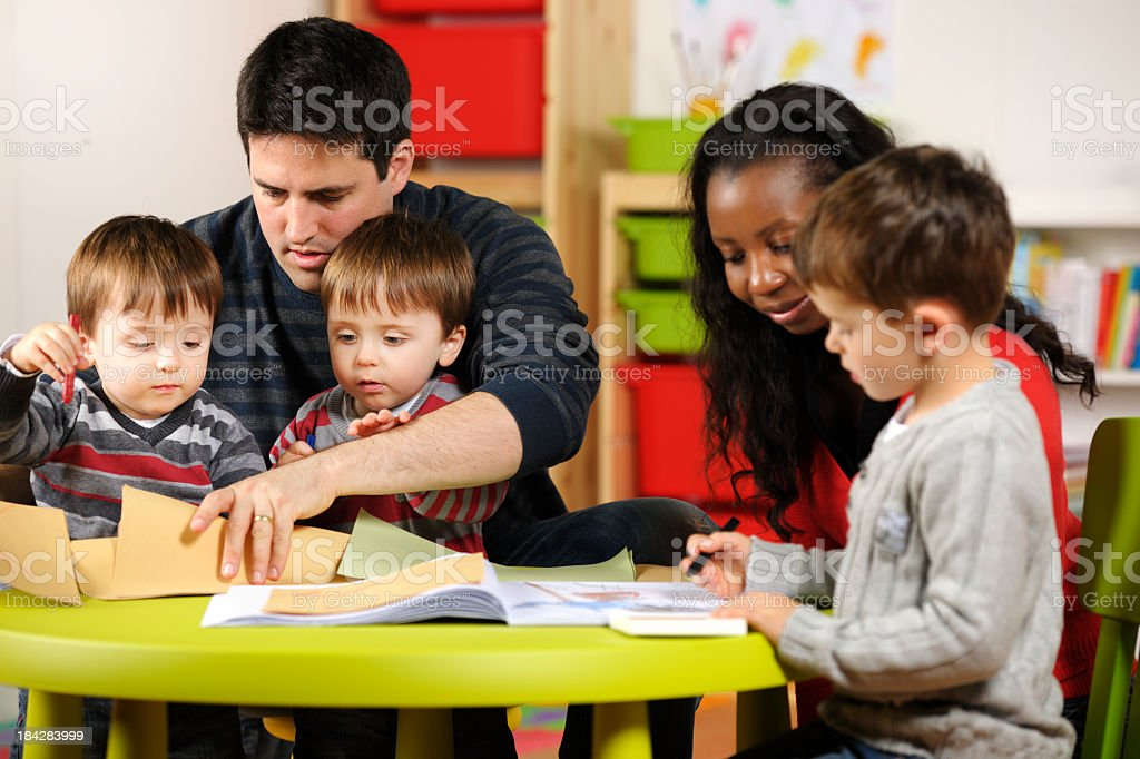 Carers/ Childminders/ TeachersSupervising Group Of Toddlers And Little Boy royalty-free stock photo
