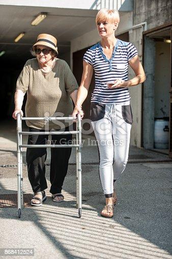 istock Caretaker Accompanying Senior Woman For A Walk Outside The Nursing Home 868412524