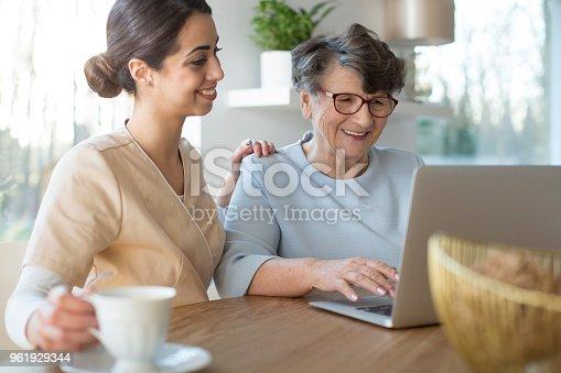 istock Caretaker and senior with laptop 961929344