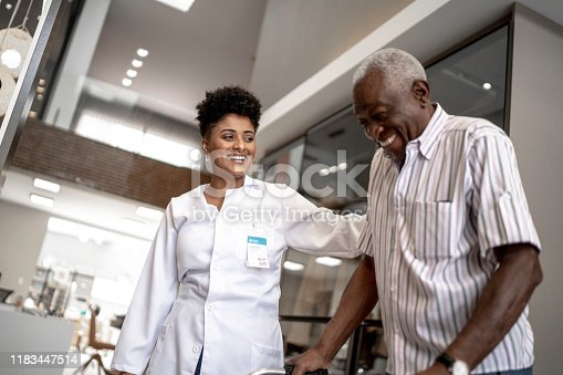 Caretaker assisting senior man with walker