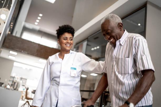 Caretaker assisting senior man with walker stock photo