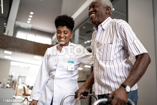 istock Caretaker assisting senior man with walker 1183448049