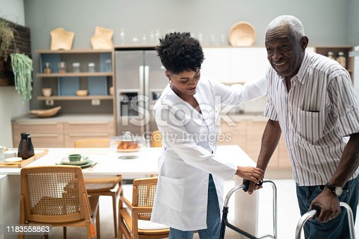 istock Caretaker assisting senior man with walker 1183558863