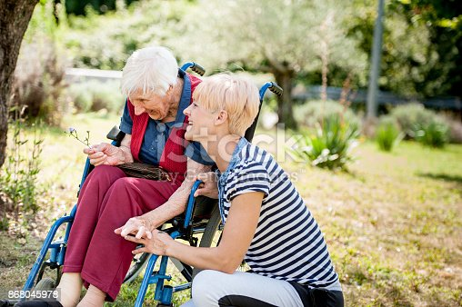 istock Caretaker Chating With Senior Woman On Wheelchair At The Back Yard Of The Nursing Home 868045978