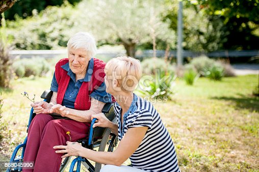 istock Caretaker Chating With Senior Woman On Wheelchair At The Back Yard Of The Nursing Home 868045990
