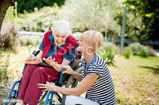 istock Caretaker Chating With Senior Woman On Wheelchair At The Back Yard Of The Nursing Home 868045994