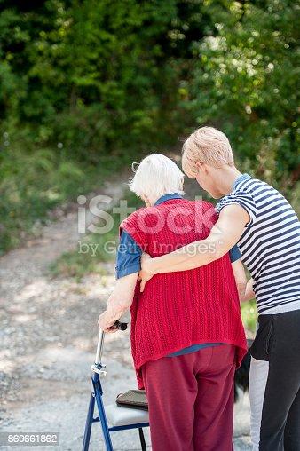 istock Caretaker Helping Senior Woman Walking Outdoor 869661862