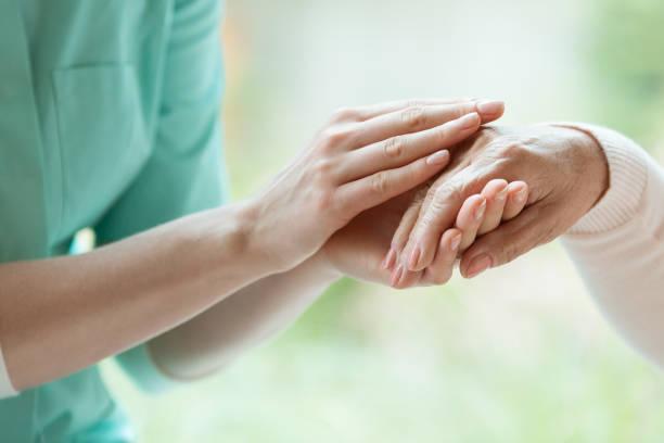 Caretaker massaging pensioner's hand stock photo