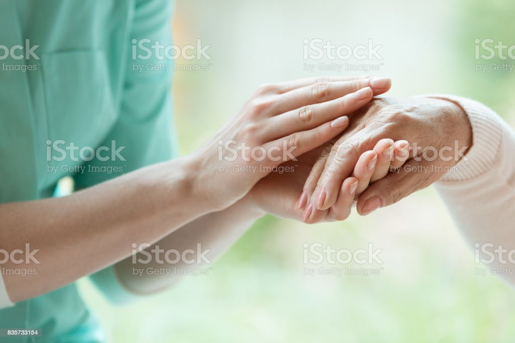 Caretaker massaging pensioner's hand - foto stock