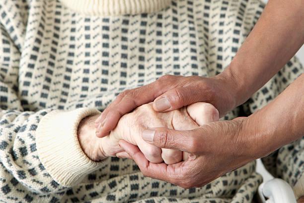 guardiano patting anziani mans mano - fragilità foto e immagini stock