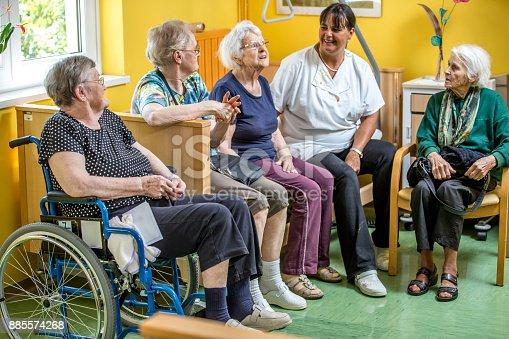 istock Caretaker Socializing With Senior Women In The Bedroom Of The Nursing Home 885574268