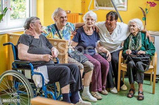 istock Caretaker Socializing With Senior Women In The Bedroom Of The Nursing Home 885574272