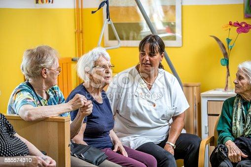 istock Caretaker Socializing With Senior Women In The Bedroom Of The Nursing Home 885574310