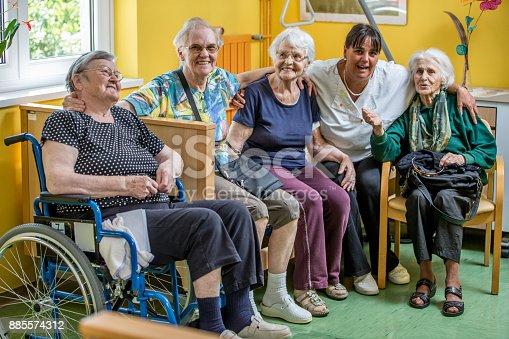 istock Caretaker Socializing With Senior Women In The Bedroom Of The Nursing Home 885574312