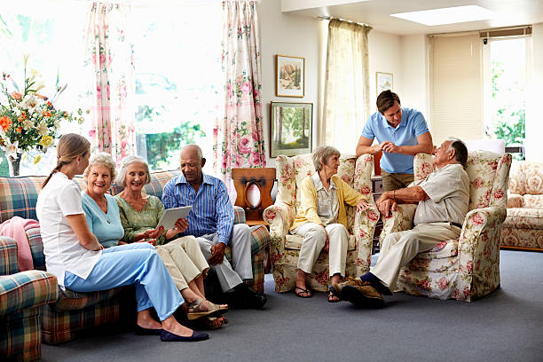 Caretaker with retired people in nursing home Male caretaker spending leisure time with retired people in nursing home retirement community stock pictures, royalty-free photos & images