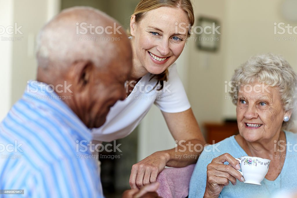 Happy female caretaker with senior people having coffee in nursing...