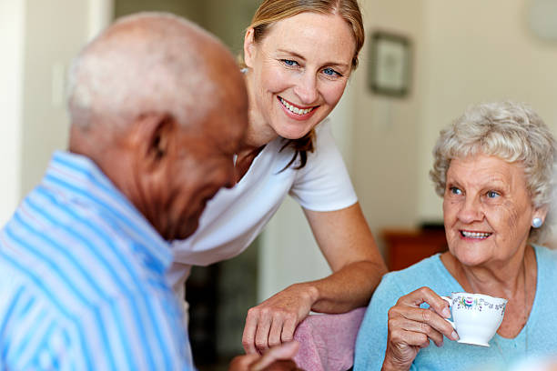 Caretaker with senior people in nursing home Happy female caretaker with senior people having coffee in nursing home retirement community stock pictures, royalty-free photos & images