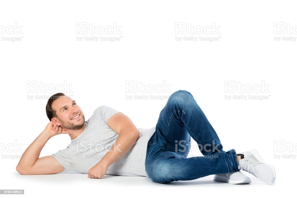Carfree man laying on the floor, thinking. stock photo