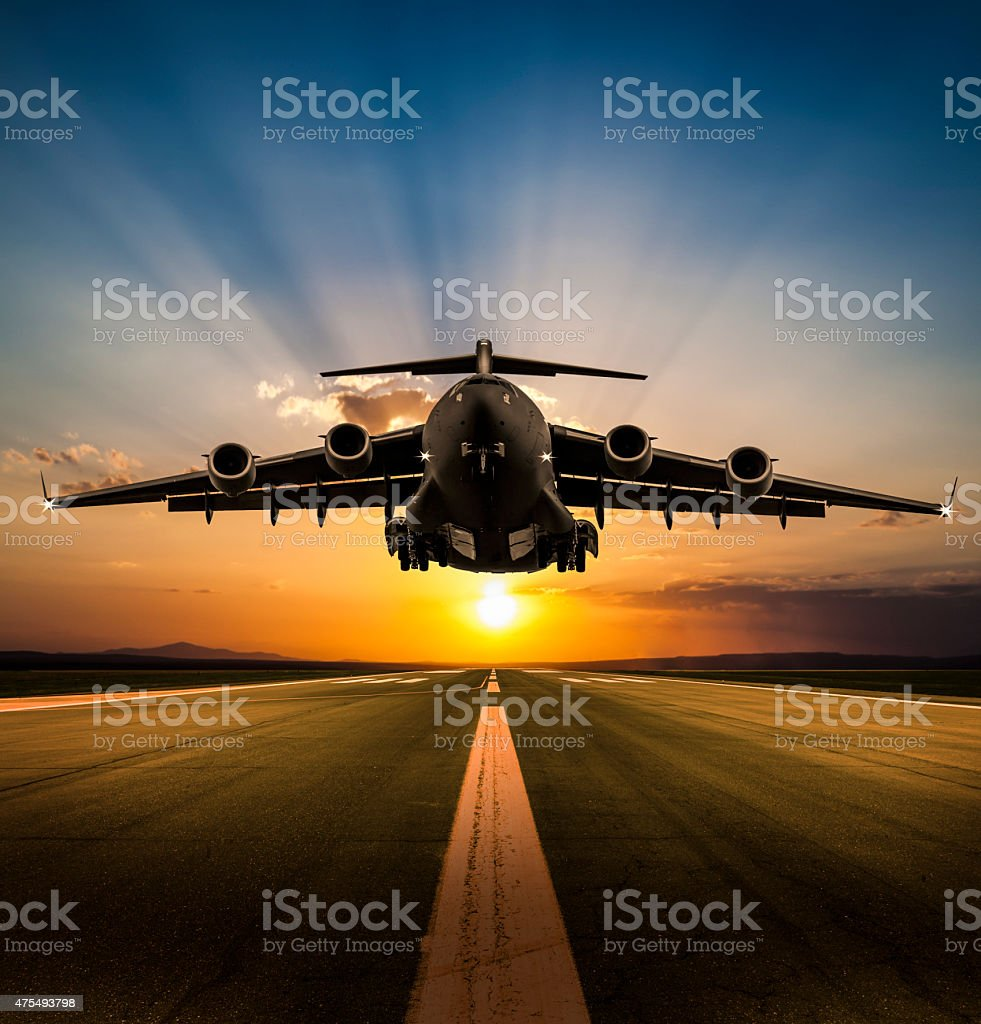Cargo Airplane landing at sunset stock photo