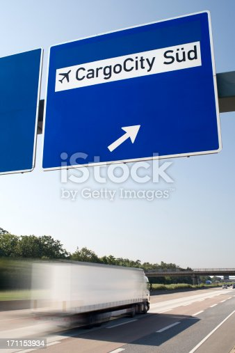 Cargo City Sued - Road sign on German Highway. Truck passes by, motion blur