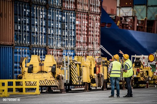 Two commercial dock workers looking into containers, possibly damaged, copy space.