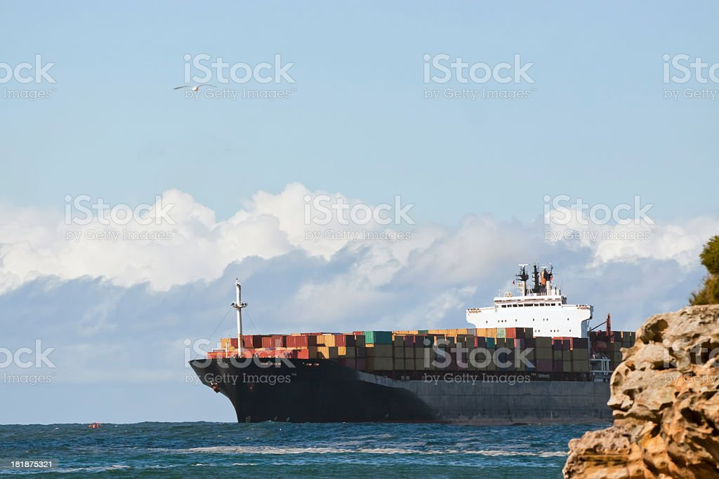 Cargo container ship against sky with clouds, copy space royalty-free stock photo