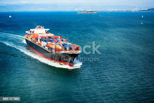 A large ship transporting numerous cargo containers through San Francisco Bay heading out to sea.