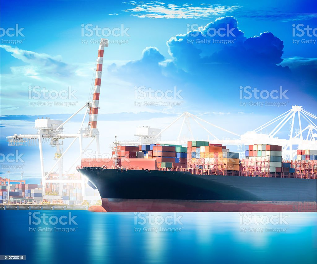 Cargo Container Ship with working crane bridge in shipyard stock photo