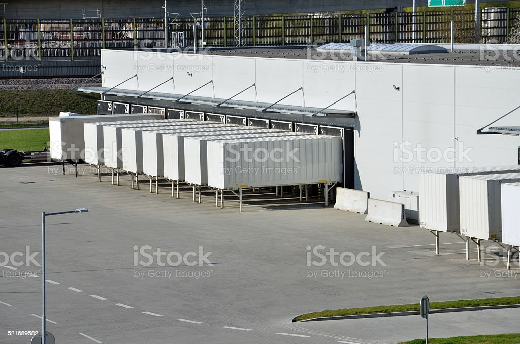 Cargo containers standing on gates in logistics center stock photo