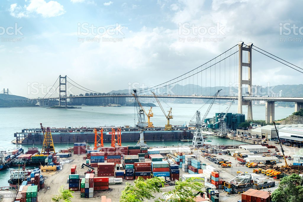 Cargo freight ship with working crane in shipyard Singapore stock photo